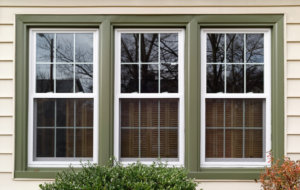 Three new replacement windows with green trim on front of house. Horizontal